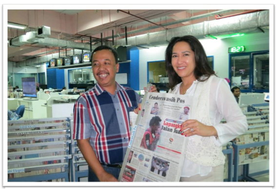 Kartika and Arif Santoso, Kepala Liputan (Chief of News Coverage) posing in front of Jawa Pos' countless local papers.